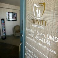 Signage on glass pane on the entrance door at Trinity Family Dental