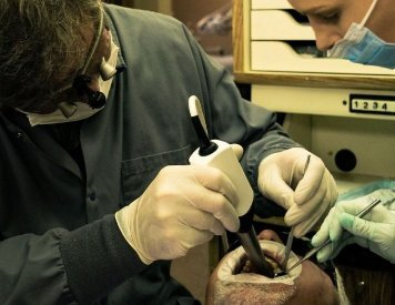 Dr. Jason Keefe performing periodontal therapy at his Spokane clinic 5 Mile Smiles